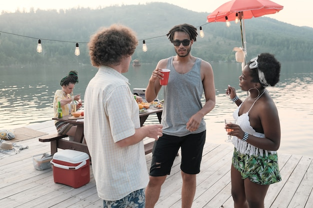 Group of young people drinking cocktails and talking to each other while standing on pier outdoors