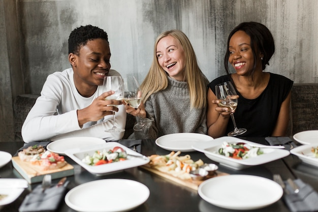 Group of young people enjoying dinner and wine