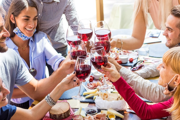 Group of young people enjoying time drinking red wine at restaurant with face mask