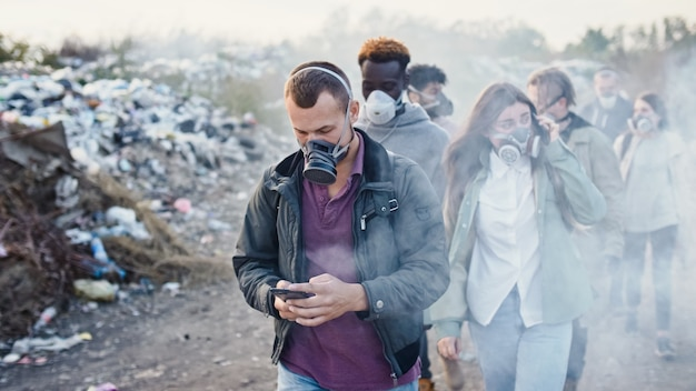 Group of young people in gas masks going through the toxic smoke in a garbage dump. people care about ecology. young activists in action against pollution stay at a landfill site. saving the planet.