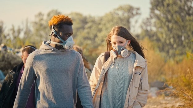 Group of young people in gas masks going through the toxic smoke in a garbage dump