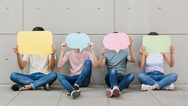 Group of young people holding speech bubbles