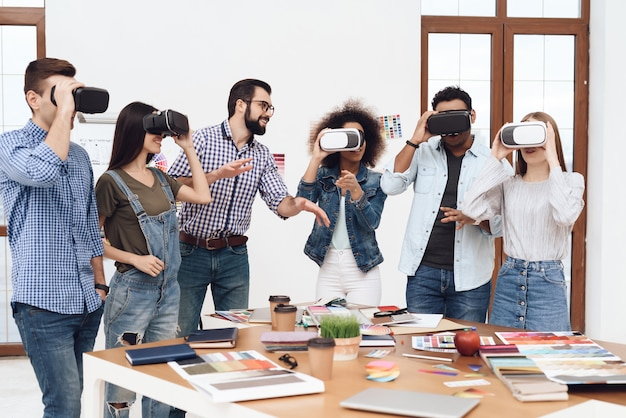 A group of young people look into virtual reality glasses.