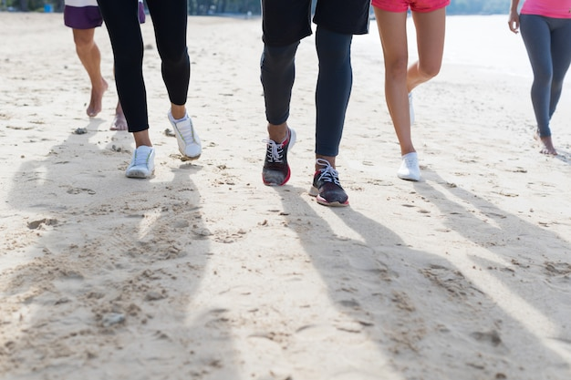 Group of young people running on beach feet closeup sport runners jogging working out team training