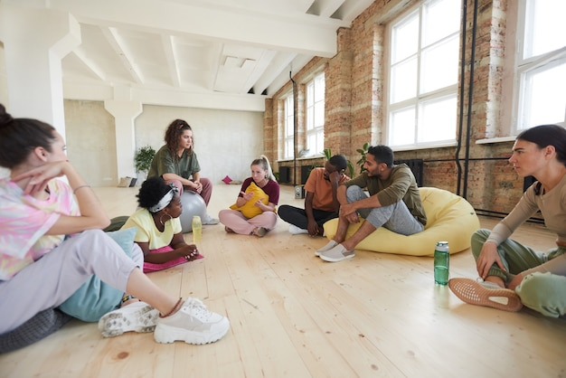 Group of young people sitting on the floor discussing new dance together in dance studio