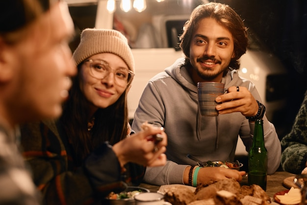 Group of young people sitting at the table and having dinner together outdoors