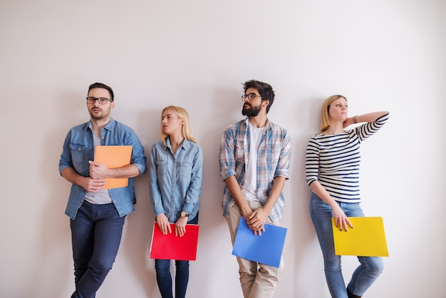 Group of young people standing in line with folders in hands. serious facial expression, in background white wall. start up business concept.