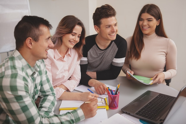 Group of young people studying together at college classroom
