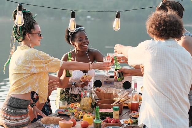 Group of young people toasting with beer at the table during their picnic on fresh air