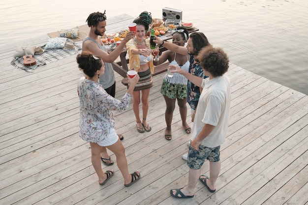 Group of young people toasting with cocktails and beer and celebrating together at a party on a pier