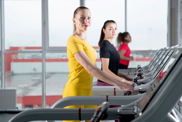 Group of young people walking on treadmills in modern sport gym