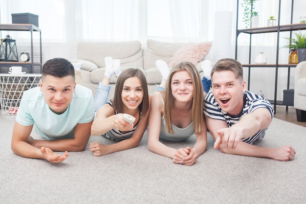 Group of young people watching tv. emotional friends having fun and watching game indoors.