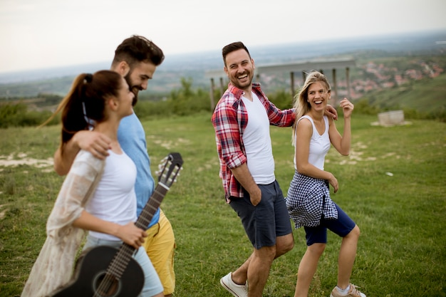 Group of young people with acoustic guitar walking in the summer field