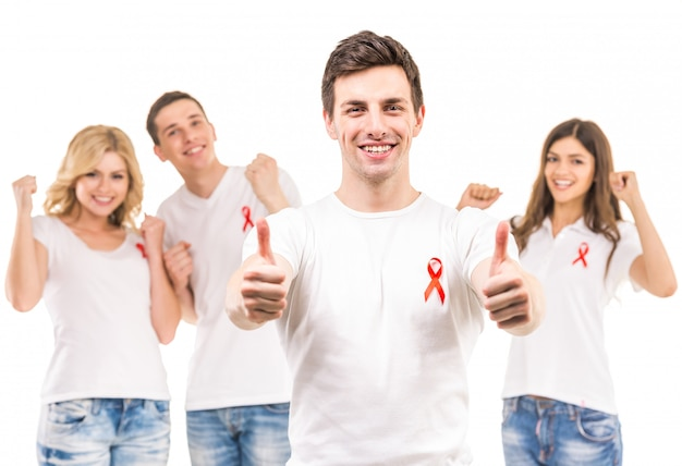 Group of young positive people with red ribbon.