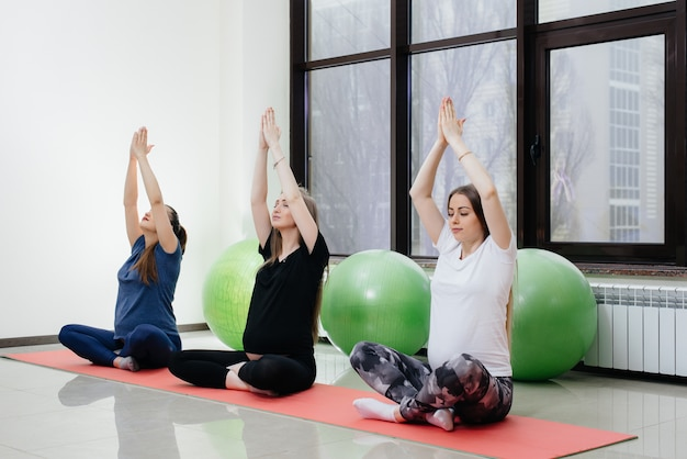 A group of young pregnant girls do yoga and sports on indoor mats. healthy lifestyle