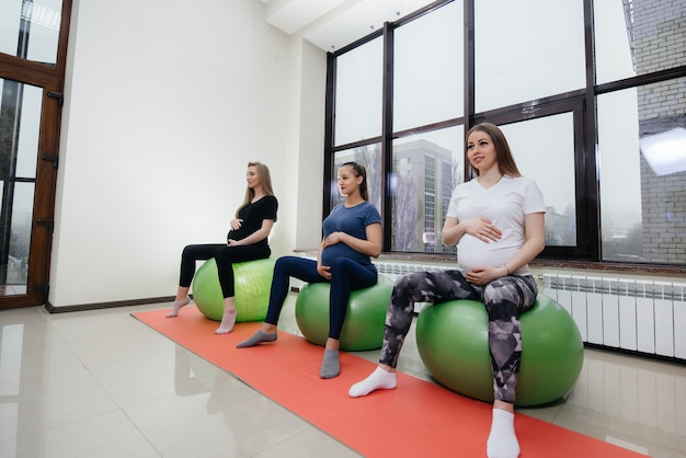 A group of young pregnant mothers are engaged in pilates and ball sports at a fitness club. pregnant