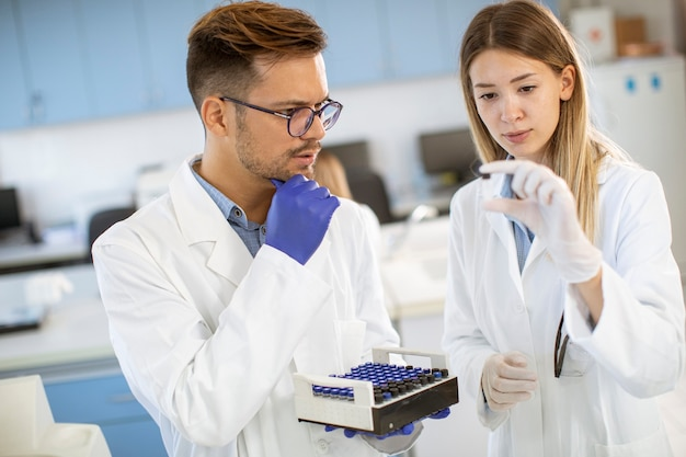 Group of young researchers analyzing chemical data in the laboratory