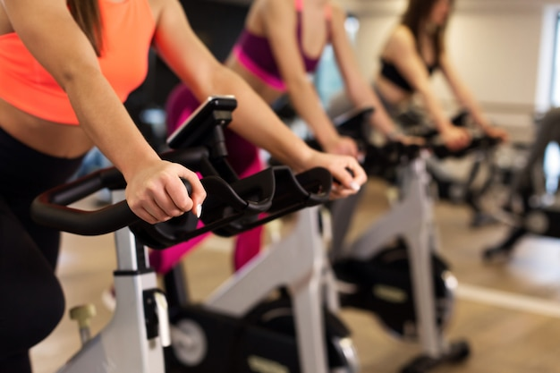 Group of young slim women workout on exercise bike in gym.