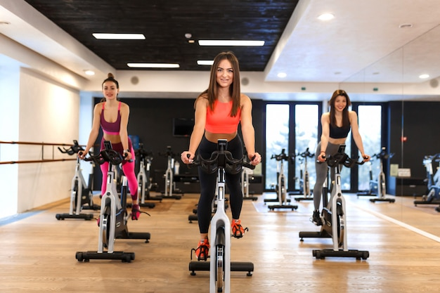 Group of young slim women workout on exercise bike in gym