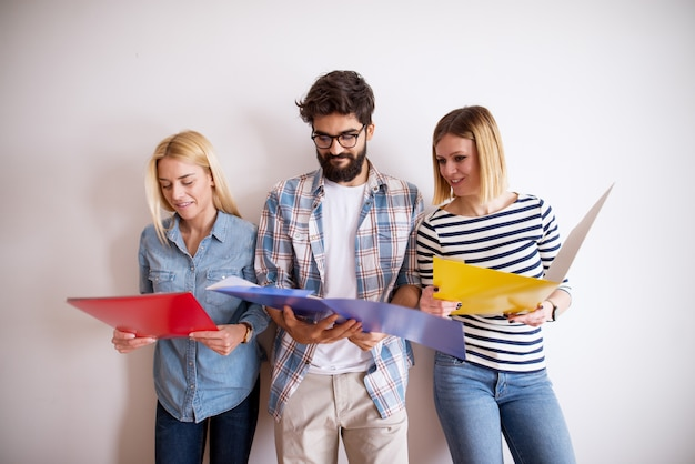 Group of young smart people leaning against the wall and looking at folders in the waiting room.