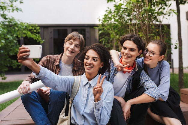 Group of young smiling students sitting and taking cute photos on cellphone while spending time together in courtyard of university