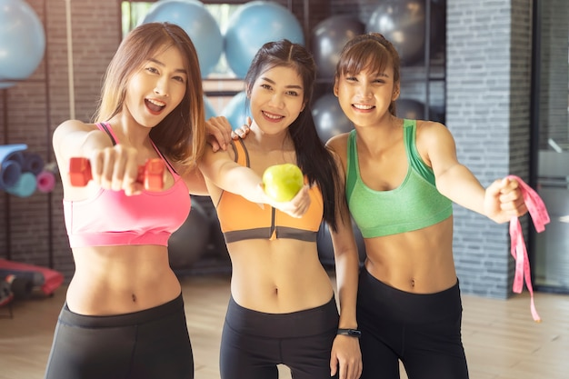 Group of young sport women in gym, showing dumbbell, green apple and tape