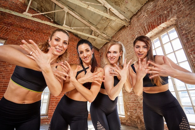 Group of young sports girls resting after a workout in a spacious loft studio female friendship in the gym