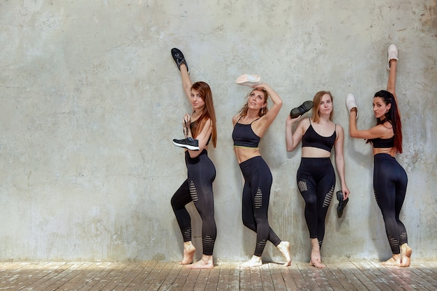 Group of young sports girls resting after a workout in a spacious loft studio.