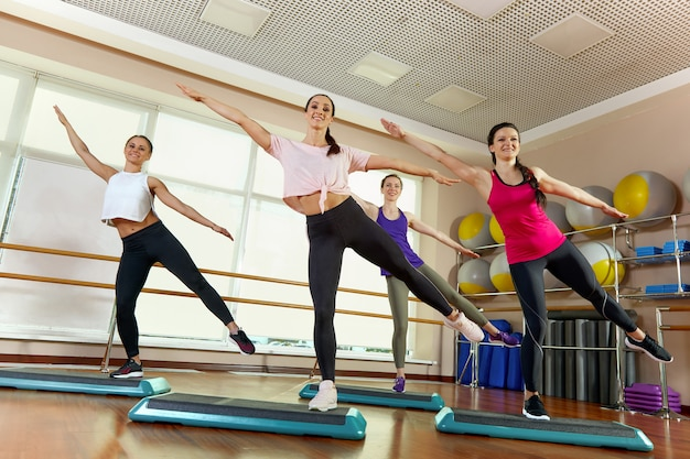 Group of young sporty attractive people practicing yoga lesson with instructor, standing together in exercise, working out, full length