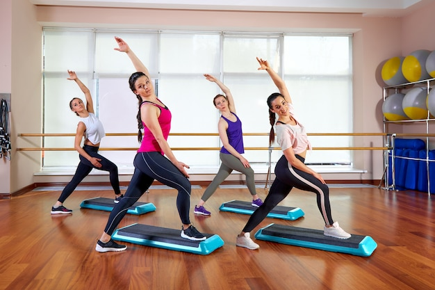 Group of young sporty attractive people practicing yoga lesson with instructor