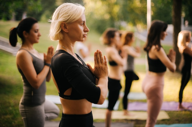 Group of young sporty european women are standing in tree pose or vrikshasana in city park on summer sunny morning.