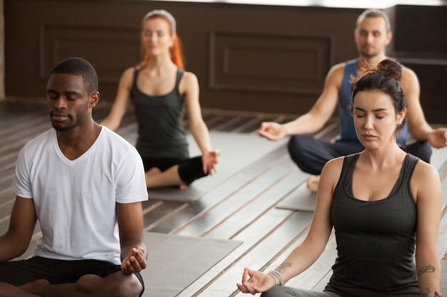 Group of young sporty people meditating in easy seat pose