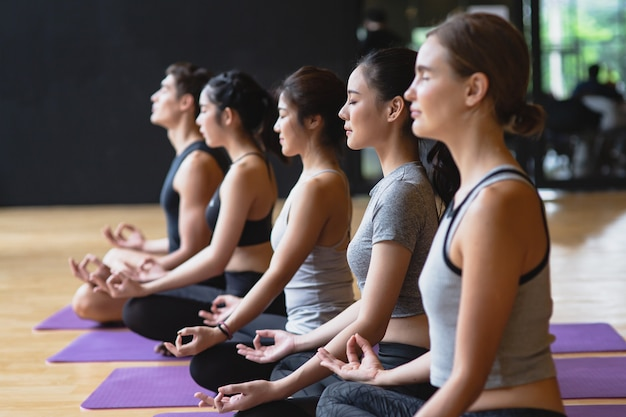 Group of young sporty people practicing yoga class making meditation lotus pose with copy space