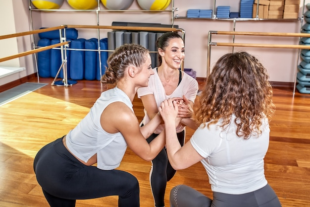 Group of young sporty people practicing yoga lesson with instructor, doing warrior two exercise, working out, indoor session full length, students training in club, studio