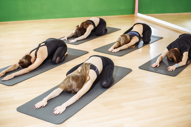 Group of young sporty people practicing yoga lesson with instructor