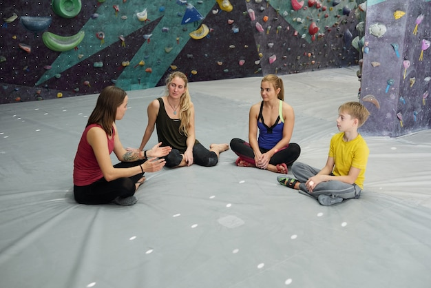 Group of young sporty people sitting on grey mat and looking at their climbing instructor while listening to her advice