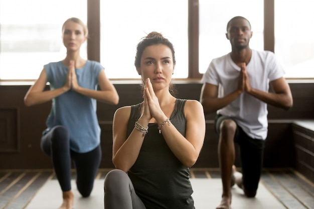Group of young sporty people standing in anjaneyasana