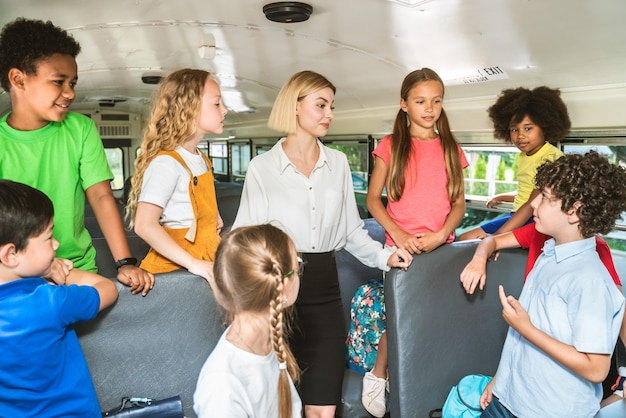 Group of young students attending primary school on a yellow school bus - elementary school kids ha1ving fun
