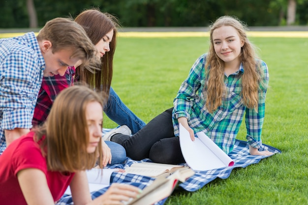 Group of young students learning in park