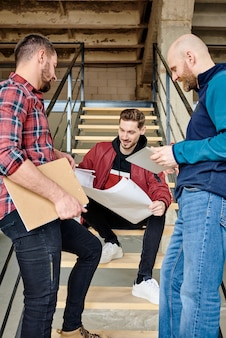 Group of young successful modern builders or architects discussing blueprint held by one of them and consulting about its details