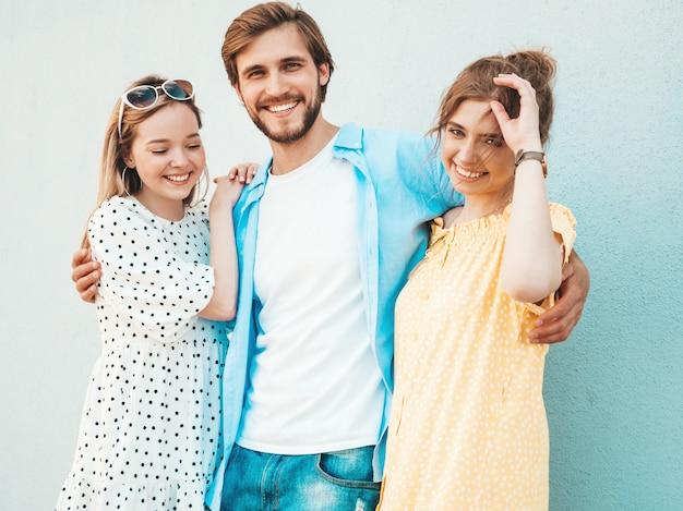 Gruppo di giovani tre amici alla moda che posano nella via. moda uomo e due ragazze carine vestite in abiti estivi casual. modelli sorridenti divertendosi vicino alla parete donne e tipo allegri all'aperto