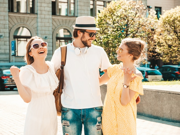 Gruppo di giovani tre amici alla moda che posano nella via. moda uomo e due ragazze carine vestite in abiti estivi casual. modelle sorridenti divertendosi in occhiali da sole. donne allegre e ragazzo che chiacchierano Foto Gratuite
