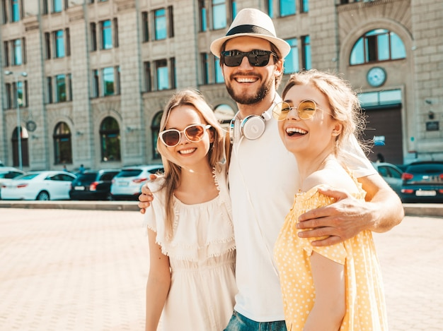 Group of young three stylish friends posing in the street. fashion man and two cute girls dressed in casual summer clothes. smiling models having fun in sunglasses.cheerful women and guy going crazy
