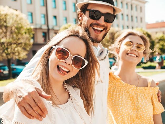 Gruppo di giovani tre amici alla moda che posano nella via. moda uomo e due ragazze carine vestite in abiti estivi casual. modelli sorridenti divertendosi in occhiali da sole. donne allegre e ragazzo che impazziscono Foto Gratuite