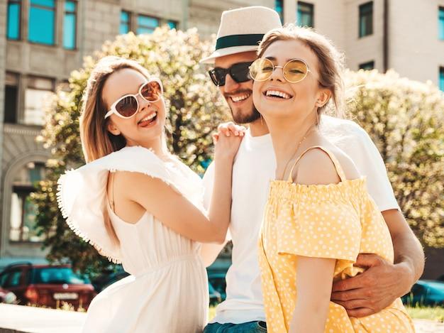 Gruppo di giovani tre amici alla moda che posano nella via. moda uomo e due ragazze carine vestite in abiti estivi casual. modelli sorridenti divertendosi in occhiali da sole. donne allegre e tipo all'aperto