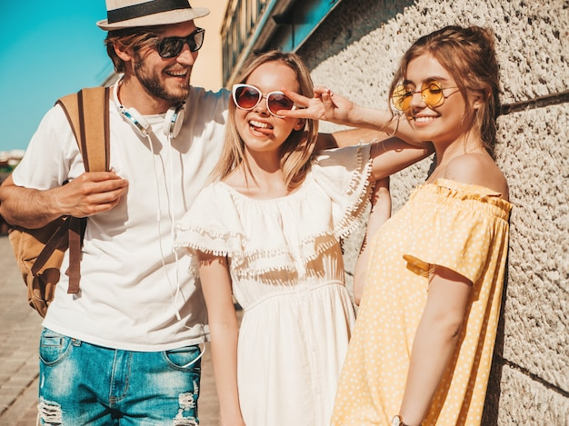 Group of young three stylish friends posing in the street. fashion man and two cute girls dressed in casual summer clothes. smiling models having fun in sunglasses.cheerful women and guy outdoors