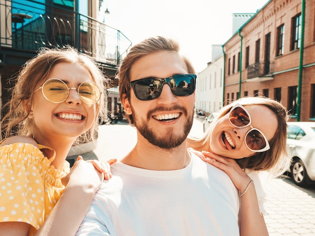 Group of young three stylish friends in the street.man and two cute girls dressed in casual summer clothes.smiling models having fun in sunglasses.women and guy making photo selfie on smartphone