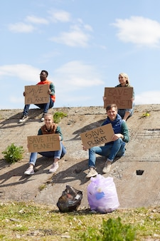 Group of young volunteers sitting on the rock with cardboard placards outdoors