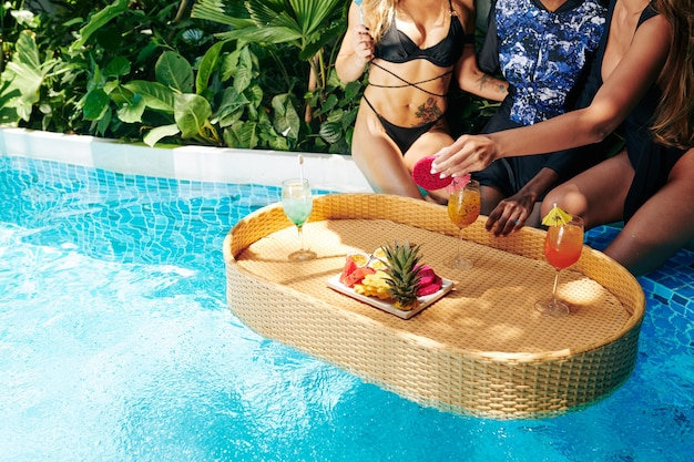 Group of young women enjoying fresh fruits and sweet delicious cocktails when enjoying hen pool party