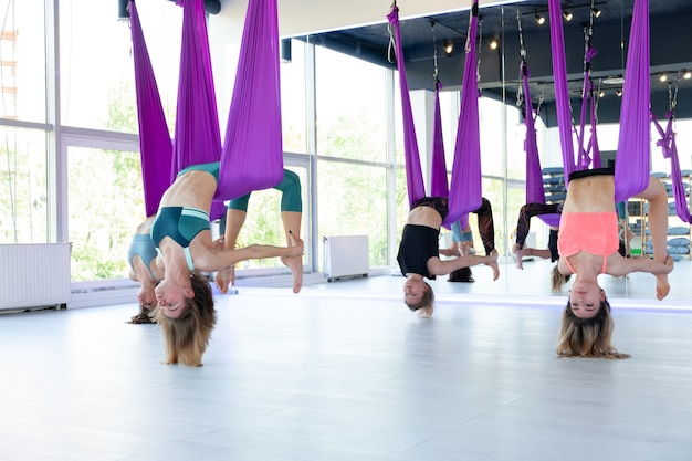 Group of young women practice in aero stretching swing. aerial flying yoga exercises practice in purple hammock in fitness club.